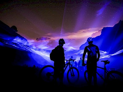 Cyclists at looking down a valley with a starry night sky background